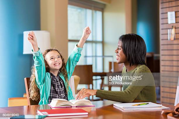 Elementary age student celebrating completing homework with tutor