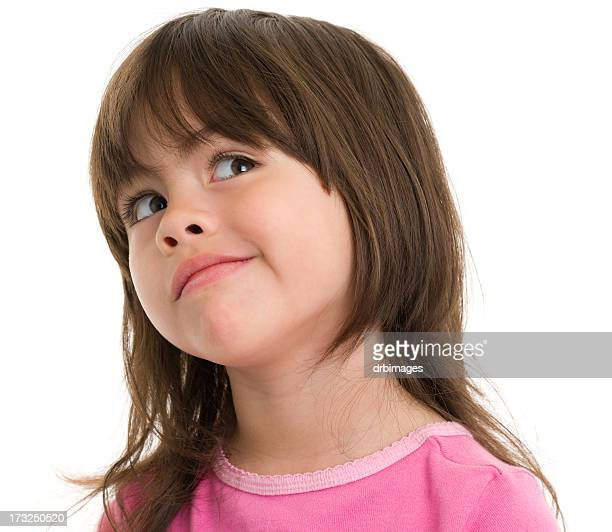 elementary aged girl looking upwards with smug smile - smug stock photos and pictures