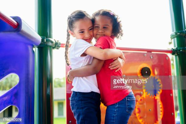 elementary aged hispanic best friends hugging on playground - playground stock pictures, royalty-free photos & images