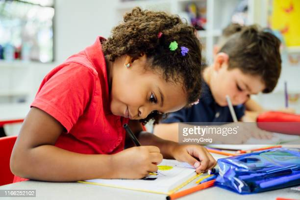 elementary aged hispanic schoolgirl focusing on her drawing - pencil case stock pictures, royalty-free photos & images