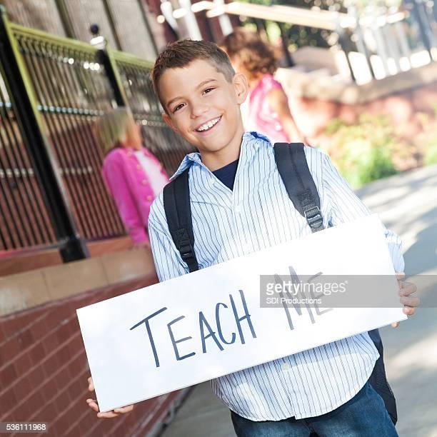 Elementary boy holding 'teach me' sign at school