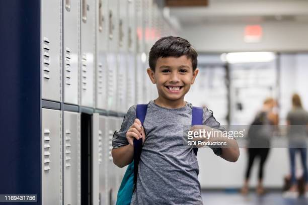 elementary boy with backpack stands by open locker - open backpack stock pictures, royalty-free photos & images