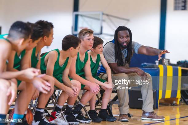 elementary boys basketball team sitting on the sideline bench with their coach - sports training camp stock pictures, royalty-free photos & images