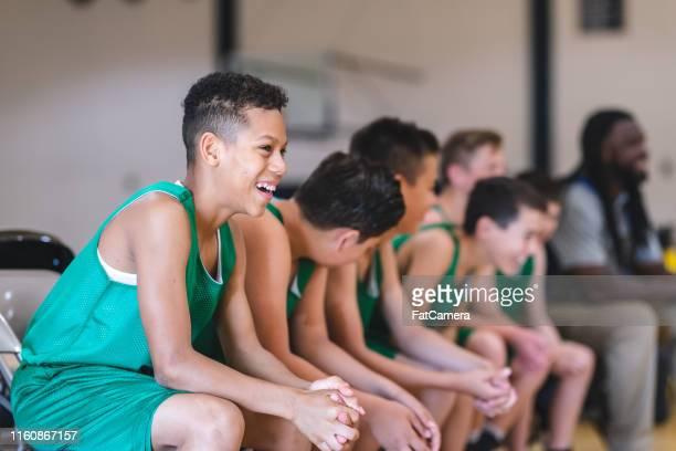 equipo de baloncesto de niños de primaria sentado en el banquillo con su entrenador - campamento de entrenamiento deportivo fotografías e imágenes de stock
