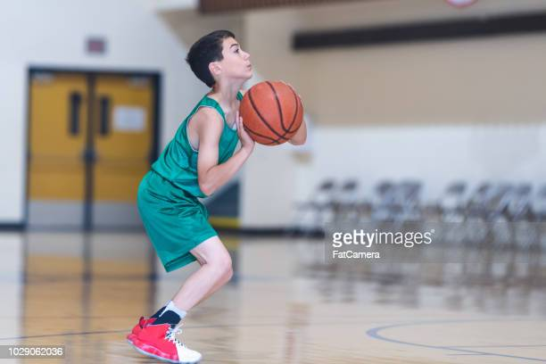 elementary boys playing basketball - sports training camp stock pictures, royalty-free photos & images