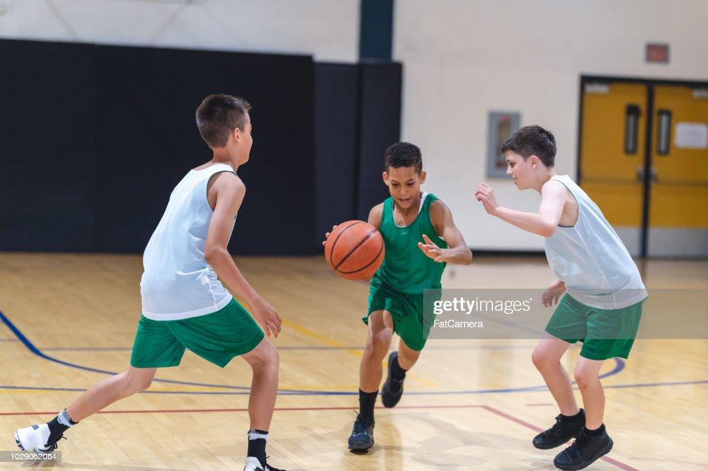 Elementary boys playing basketball : Stock Photo