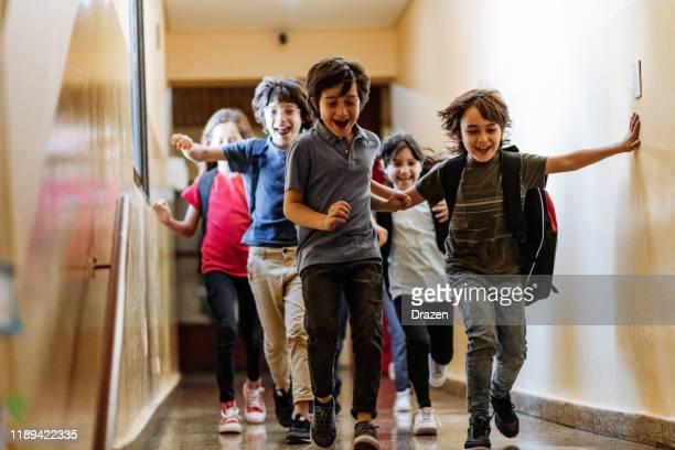 grundschulbildung in lateinamerika - kinder laufen im flur - argentinischer abstammung stock-fotos und bilder