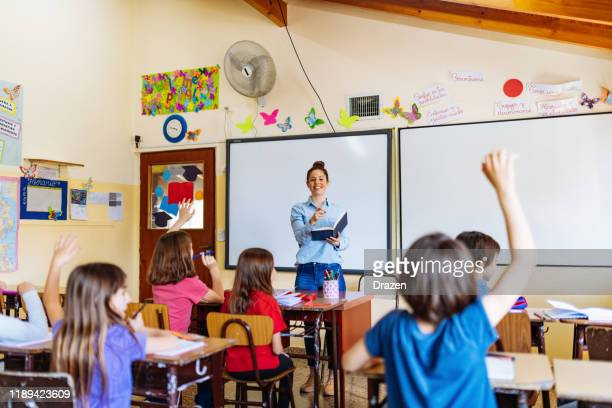 elementary education in latin america - teacher examining school children in classroom - knowledge is power stock pictures, royalty-free photos & images