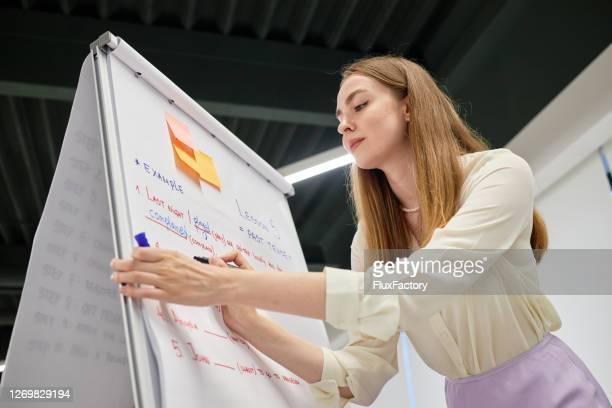 professora do ensino fundamental escrevendo um exemplo no quadro negro enquanto transmitia sua aula para os alunos - girl power provérbio em inglês - fotografias e filmes do acervo