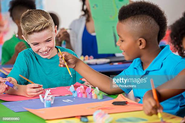 Elementary friends paint pictures in art class