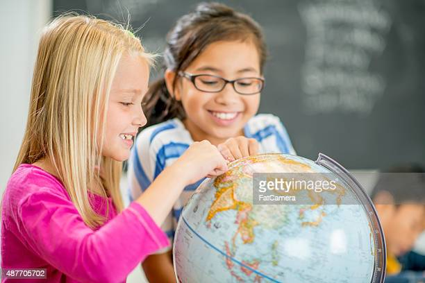 Elementary Girls Looking at a Globe