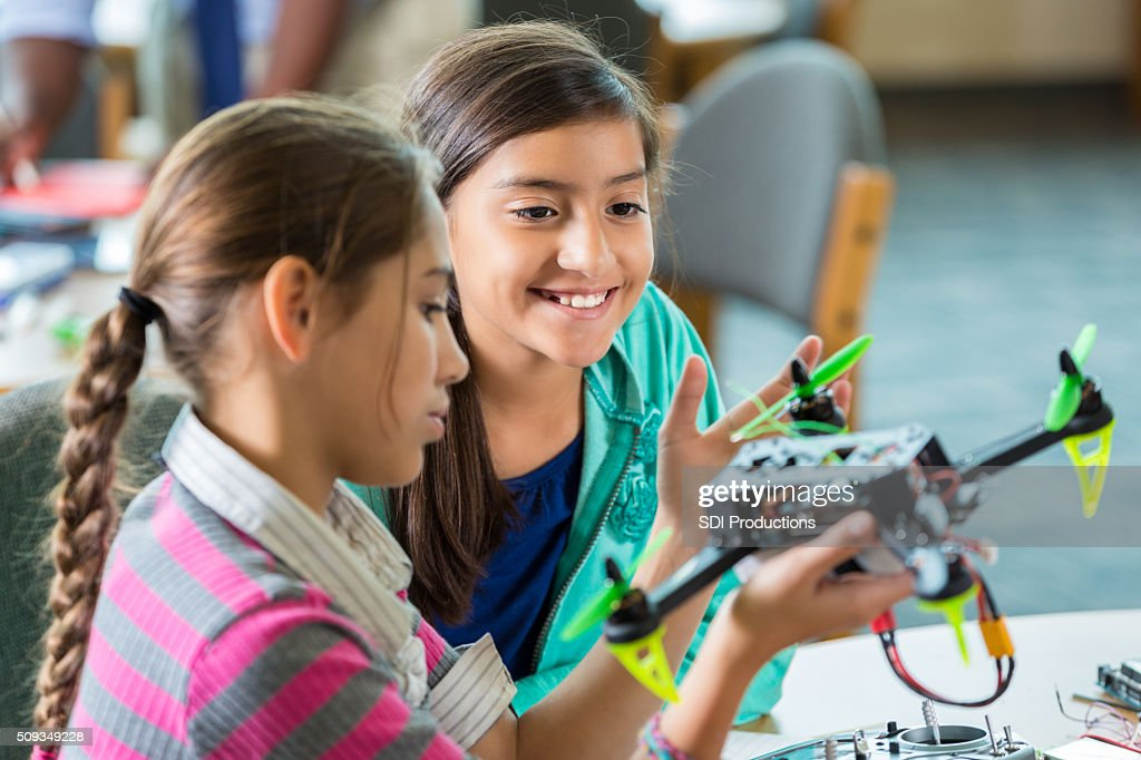 Elementary girls using drones during after school science program : Stock Photo