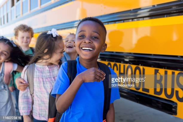 elementary school children goof off and laugh by bus - back to school stock pictures, royalty-free photos & images