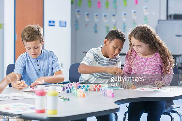 Elementary school children in art class painting