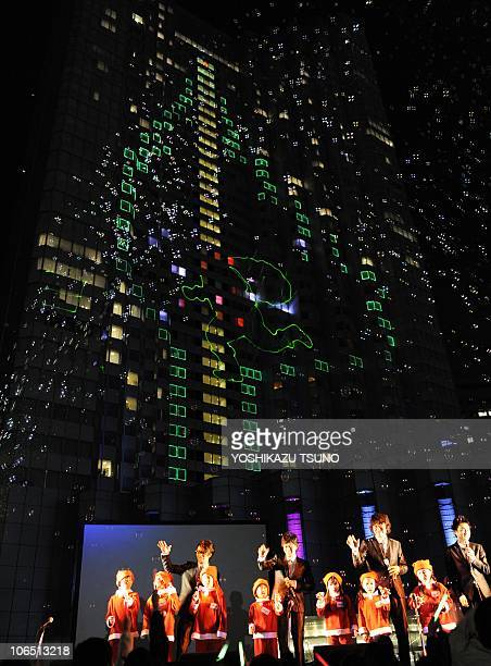 Elementary school children in Santa costumes sing for the lighting ceremony of a 100metre tall Christmas tree illuminated on the wall of Tokyo's...