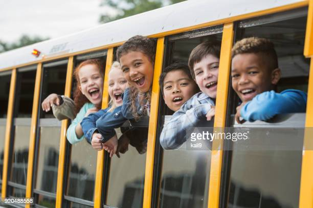 elementary school children looking out window of bus - school children stock pictures, royalty-free photos & images