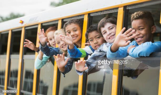 Elementary school children looking out window of bus