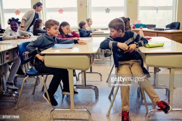 Elementary school children misbehaving in classroom.