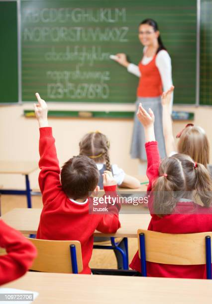 Elementary School Children Raising Hands In Class, Rear View