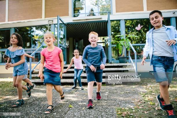 grundschulkinder laufen aus der schule, schulhof - schulkind stock-fotos und bilder