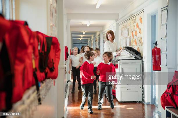 elementary school children running through the corridor - school principal stock pictures, royalty-free photos & images