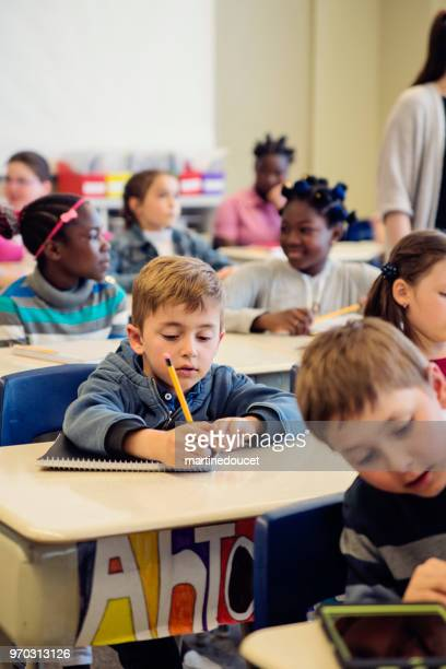 Elementary school children sitting and listening in classroom.