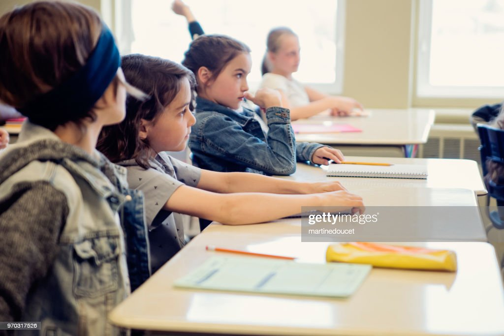 Elementary school children sitting and listening in classroom. : Stock Photo