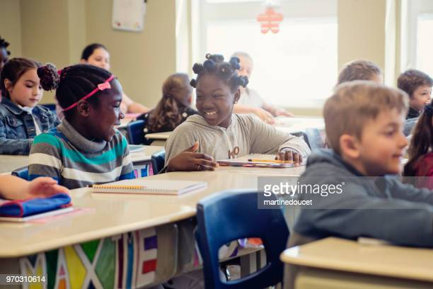 Elementary school children taking their places in classroom.