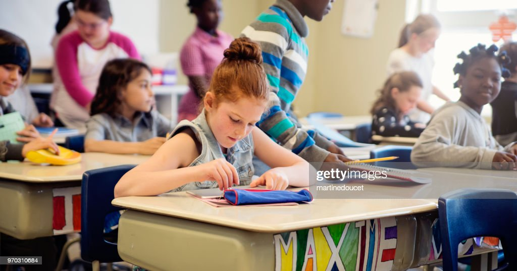 Elementary school children taking their places in classroom. : Stock Photo