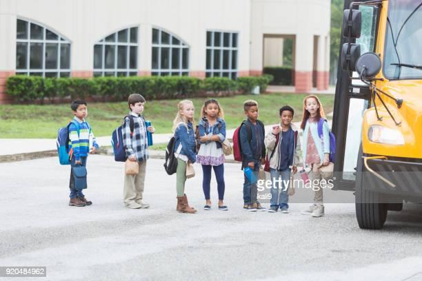 elementary school children waiting outside bus - somente crianças imagens e fotografias de stock