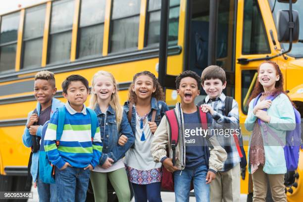 Elementary school children waiting outside bus