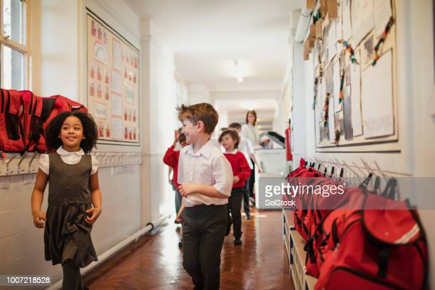 elementary school children walking through the corridor - british culture stock pictures, royalty-free photos & images