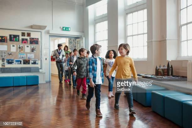 ホールを通って歩いて小学校児童 - 講堂 ストックフォトと画像