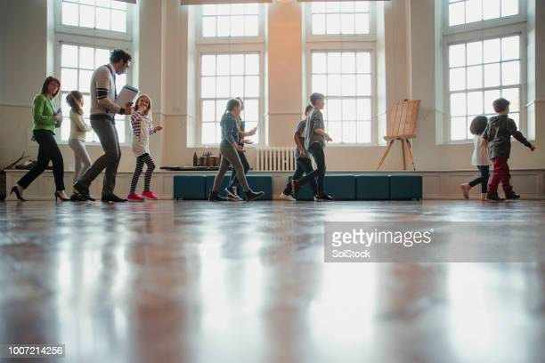 elementary school children walking through the school assembly room - corridor stock pictures, royalty-free photos & images