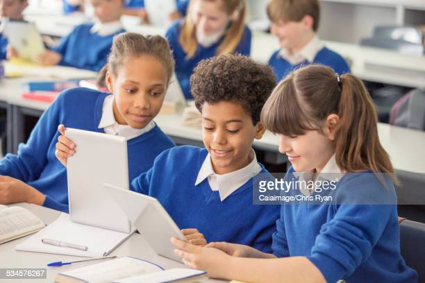 Elementary school children wearing blue school uniforms using digital tablets at desk in classroom