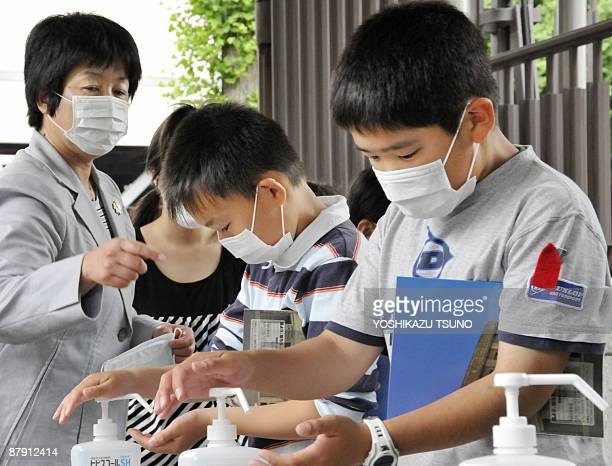 Elementary school children wearing facemasks wash their hands with disinfectant alcoholic gel as they visit the National Diet in Tokyo for a field...