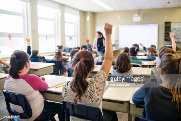 Elementary school children with arms raised in classroom.
