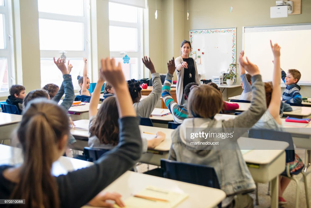 Elementary school children with arms raised in classroom. : Stock Photo