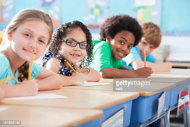 elementary school children writing in class - primary age child stock pictures, royalty-free photos & images