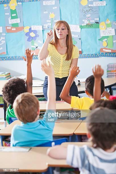 Elementary school class, raising hands