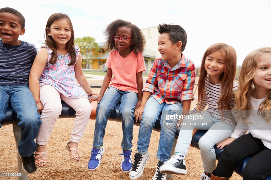 Elementary school friends sitting on a spinning carousel : Stock Photo