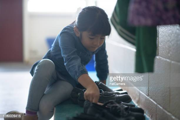 elementary school girl finding her shoes - school girl shoes stock pictures, royalty-free photos & images