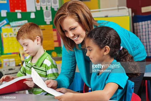 Elementary School Girl Looking at Test Paper With Teacher