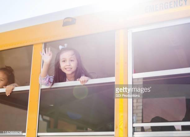 スクールバスの窓から小学校の女の子の波 - 背景に人 ストックフォトと画像
