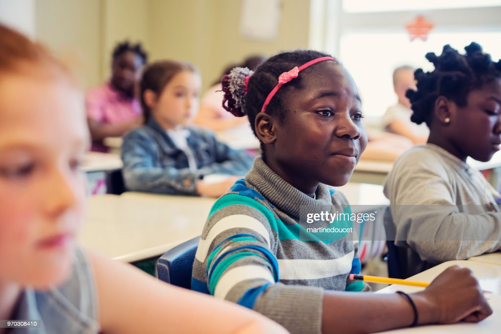 Elementary school girls sitting and listening in classroom. : Stock Photo