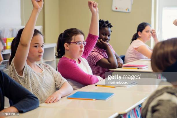 Elementary school girls with arms raised in classroom.