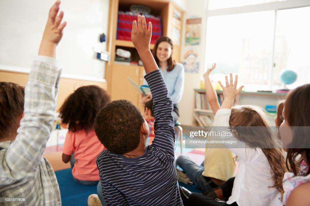 Elementary school kids raising hands to teacher, back view : Stock Photo
