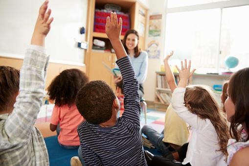 Elementary school kids raising hands to teacher, back view 1031377826