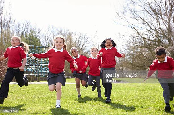 elementary school pupils running in playground at breaktime - britain playgrounds stock pictures, royalty-free photos & images