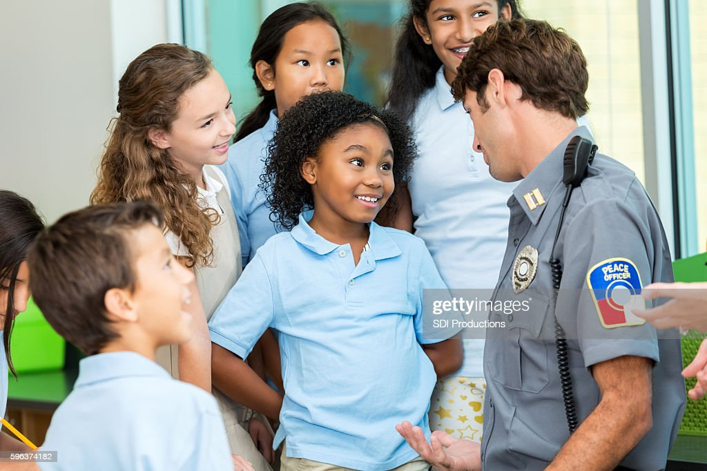Elementary school student asks policeman a question : Stock Photo